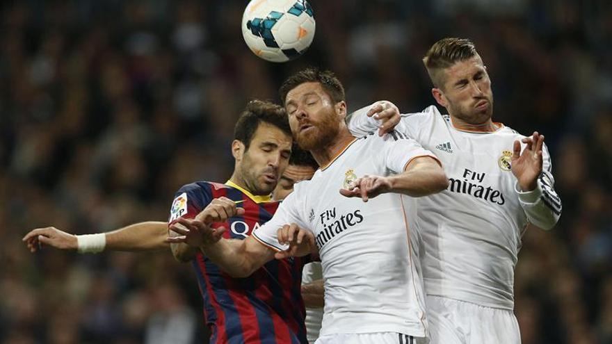 Los madridistas Xabi Alonso y Sergio Ramos disputan un balón con Cesc Fábregas. EFE / Juanjo Martín.