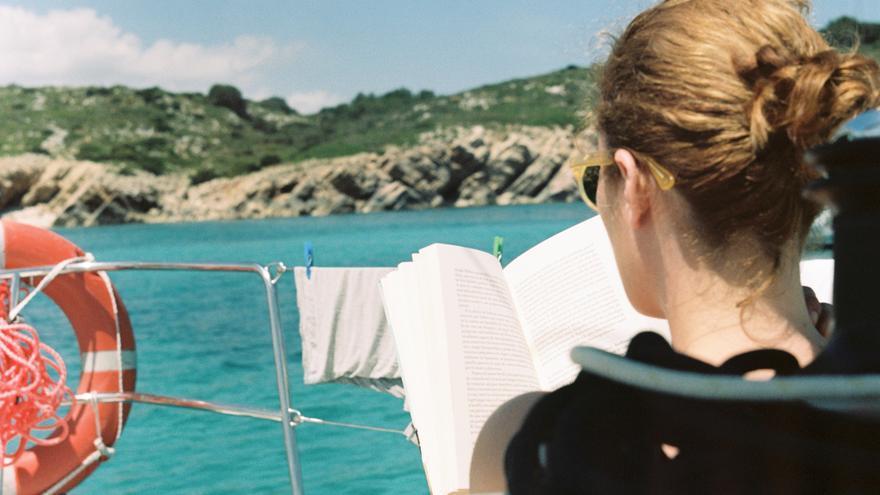 Una joven lee en un barco en Arenal d'en Castell, en Menorca