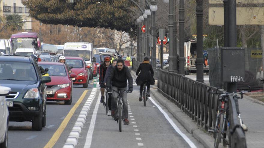Ciclistes i automòbils en un carrer de València.