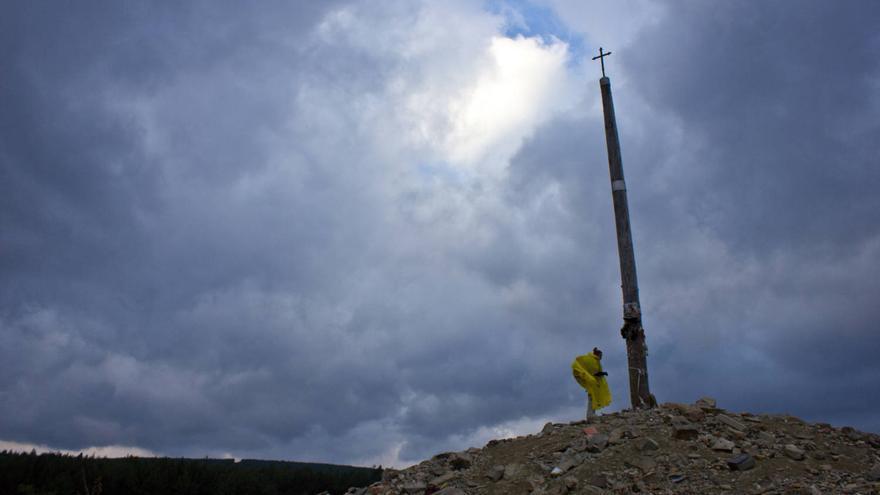Una peregrina junto a la Cruz de Ferro, en el Camino de Santiago.