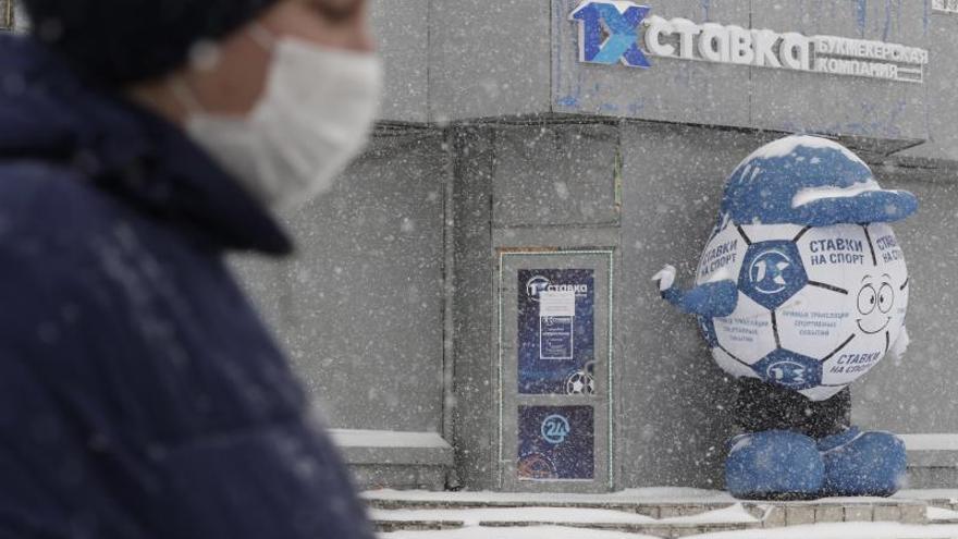 Una mujer protegida con una mascarilla, pasa ante una casa de apuestas cerrada, en un barrio residencial de Moscú.
