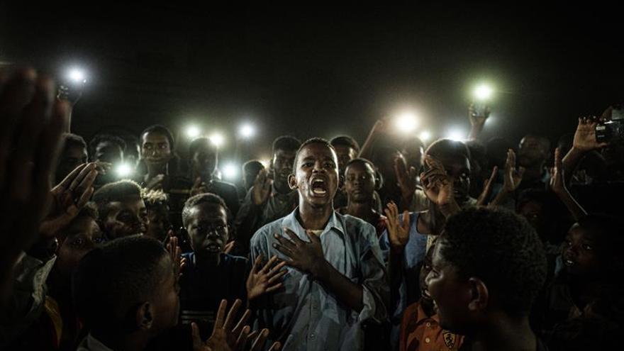 El fotógrafo japonés Yasuyoshi Chiba ha sido galardonado este jueves con el World Press Photo por su fotografía del grito pacífico de un grupo de jóvenes en Sudán, que iluminaban con sus teléfonos móviles a un chico mientras recitaba un poema.