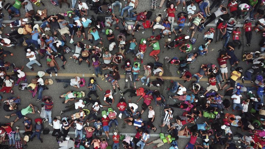 Miembros de la caravana de migrantes con destino a Estados Unidos descansan en una carretera entre los estados mexicanos de Chiapas y Oaxaca después de que la policía federal los bloqueara brevemente fuera de la ciudad de Arriaga, el 27 de octubre de 2018.