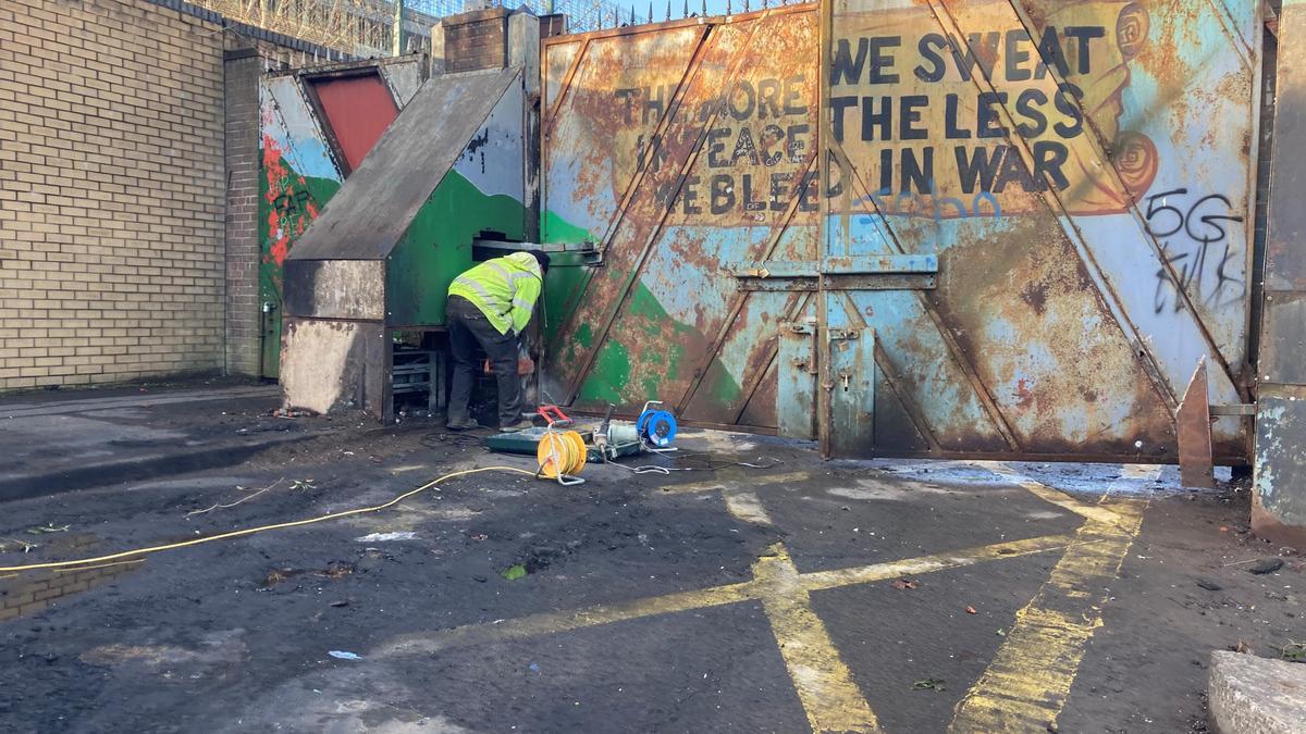 Un operario limpia los restos de los disturbios ocurridos en la puerta del 'muro de la paz' en Lanark Way, Belfast, hace unas semanas.