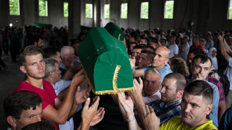 Los familiares desplazados hasta el lugar se reencuentran entonces por primera vez con el féretro de sus familiares y los hombres ayudan a sacar del camión los ataúdes para colocarlos en el suelo de la antigua fábrica donde los cascos azules holandeses tuvieron la misión de proteger a los refugiados musulmanes que se desplazaron al lugar durante el conflicto. Se estima que unas 20.000 refugiados musulmanes se instalaron en los alrededores de Srebrenica antes de producirse la masacre/ Fotografía: César Dezfuli