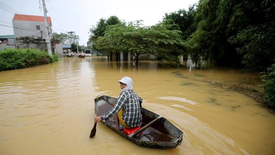 Una mujer cruza una avenida en barca en la comunidad de Hoang Van Thu, distrito de Chuong My, en Hanoi (Vietnam), por las inundaciones causadas por las fuertes lluvias caídas