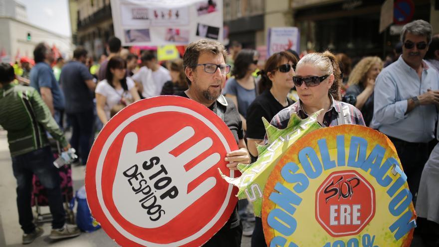 Dos manifestantes en Madrid con carteles contra los despidos y los ERE.