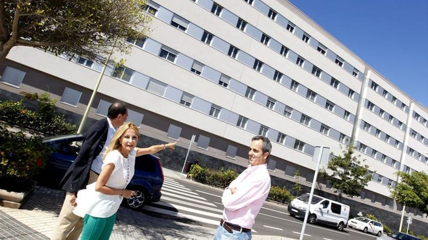 La portavoz del Partido Popular en el Parlamento autonómico, Australia Navarro (i), frente al bloque de viviendas de protección oficial del barrio de Siete Palmas, en Las Palmas de Gran Canaria. (EFE/Elvira Urquijo A.).