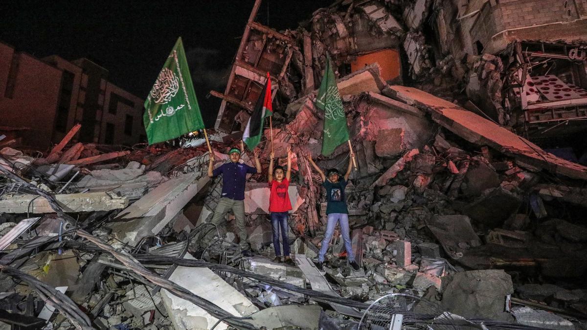 Palestinos celebran la tregua entre Israel y las milicias palestinas en medio de los escombros de un edificio en la ciudad de Gaza.