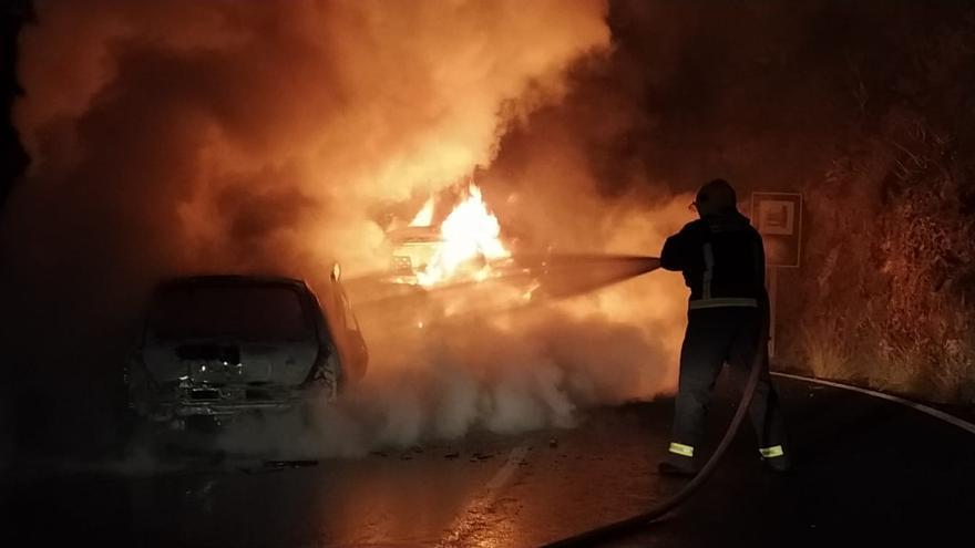 Un bombero sofocando  el incendio tras la colisión frontal de dos vehículos, en la noche de este domingo, en la carretera de El Time (Tijarafe).