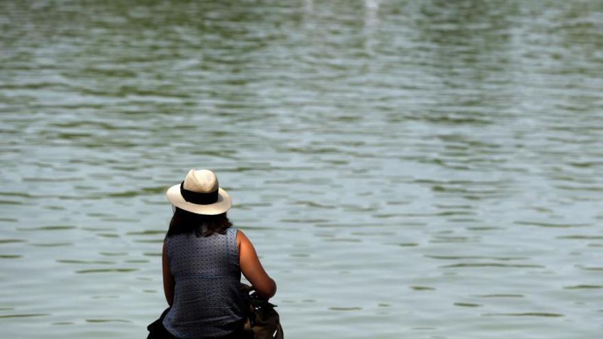 Una mujer junto al estanque del parque de El Retiro, en Madrid.