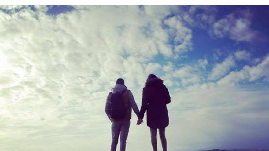 Una pareja mira al horizonte frente al mar