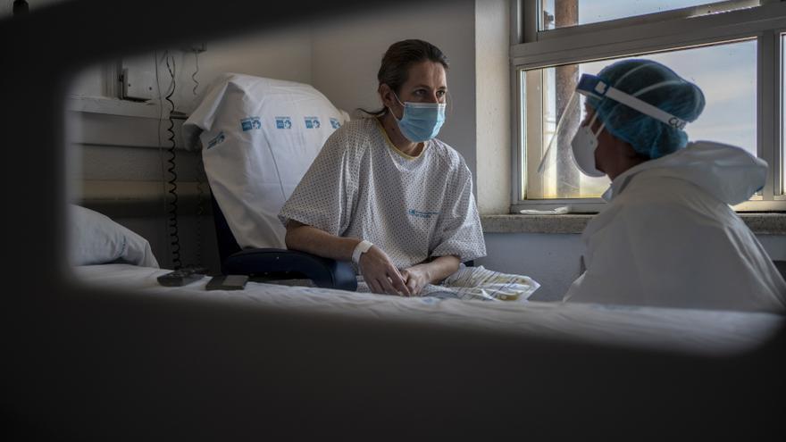 Lucía, técnico de cuidados, habla con Ana, una paciente de 41 años con COVID-19 que lleva semanas ingresada en el hospital.