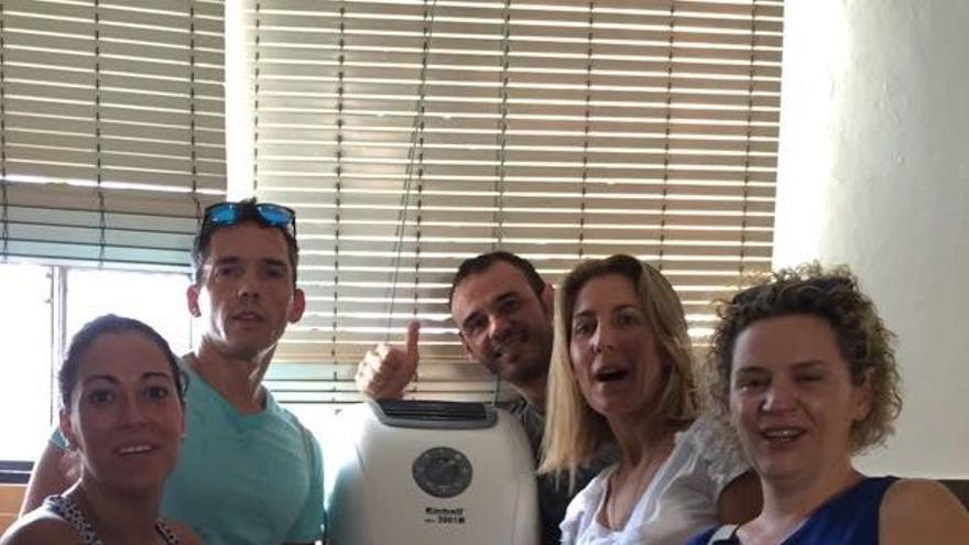 Padres y madres de un colegio de Sevilla colocando un aire acondicionado portatil