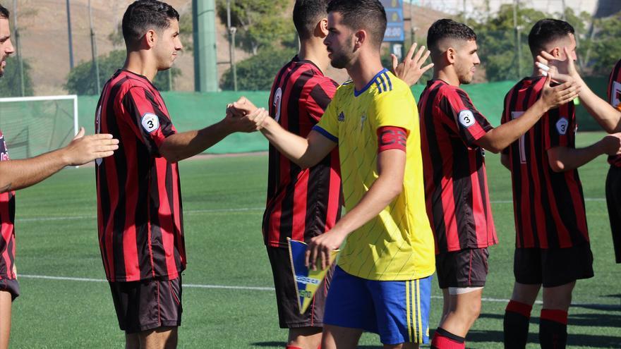 Los jugadores rojinegros y amarillos se saludan antes del inicio del partido de ida