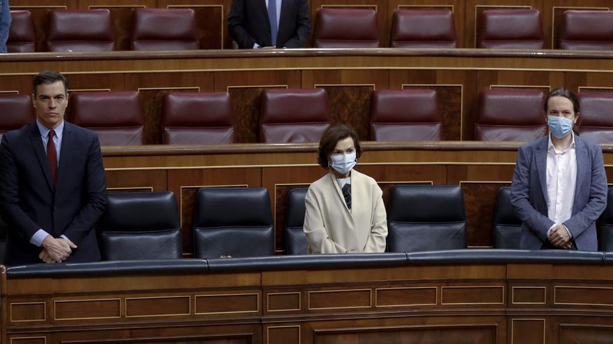El presidente del Gobierno, Pedro Sánchez, y los vicepresidentes primera, Carmen Calvo y segundo, Pablo Iglesias, durante el minuto de silencio por los más de 27.700 fallecidos que se ha cobrado la COVID-19 y que se ha guardado este miércoles en el Congreso