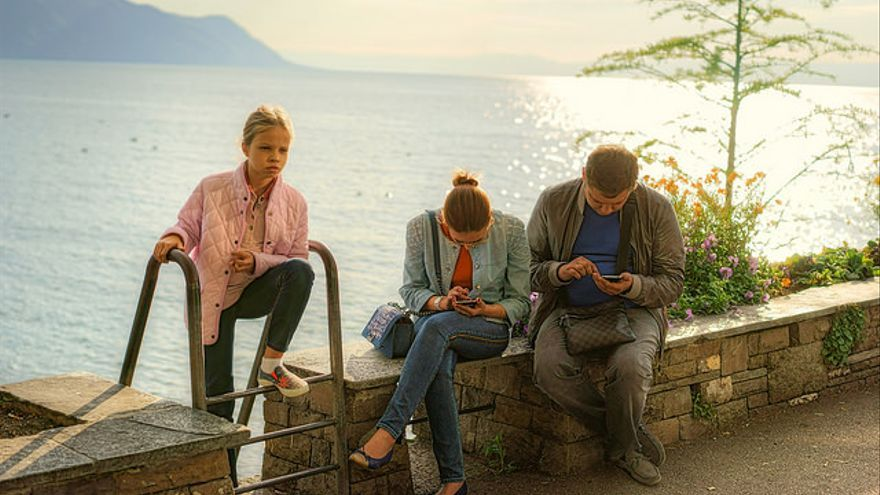 Unos padres utilizan el móvil