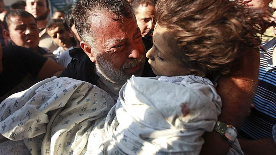 Akram Miqdad cries while holding the body of Bara-a, his six year old daughter, in Gaza City.