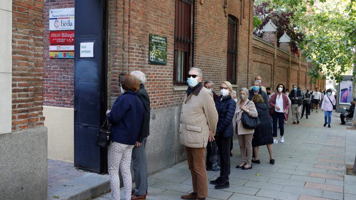 Varias personas hacen cola para ejercer su derecho al voto en el colegio electoral de Nuestra Señora de Loreto en Madrid. EFE/ Juan Carlos Hidalgo