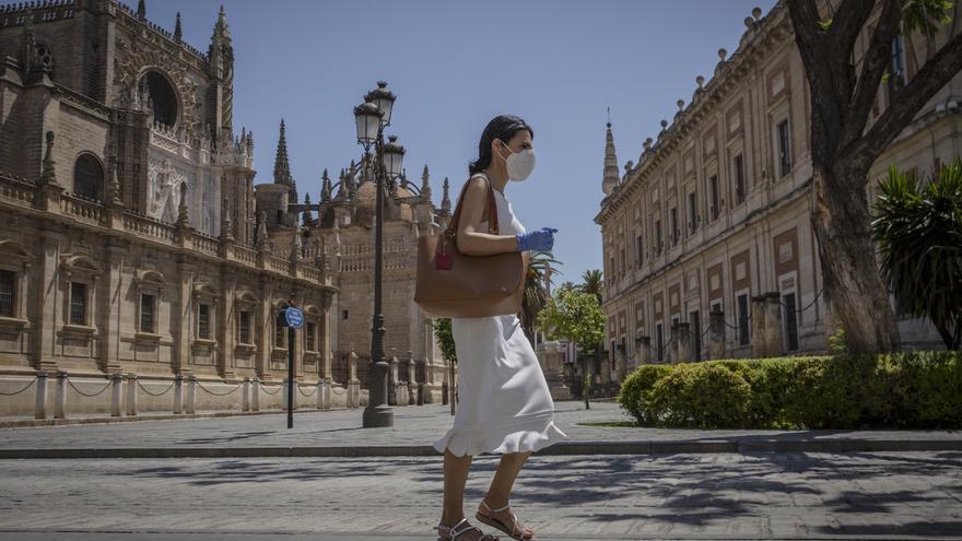 Una mujer con mascarilla y guantes caminando por una calle de Sevilla durante la fase 2.