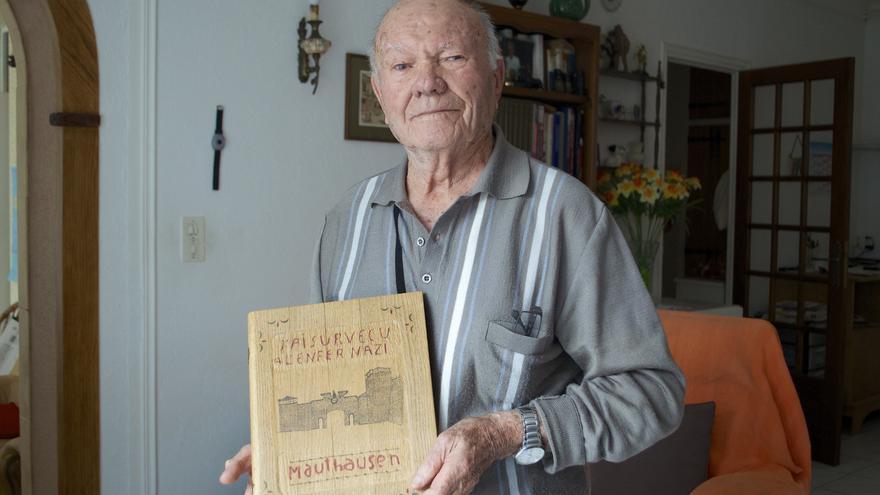 José Marfil posa con la portada de madera que él mismo fabricó para su libro Yo sobreviví al infierno nazi