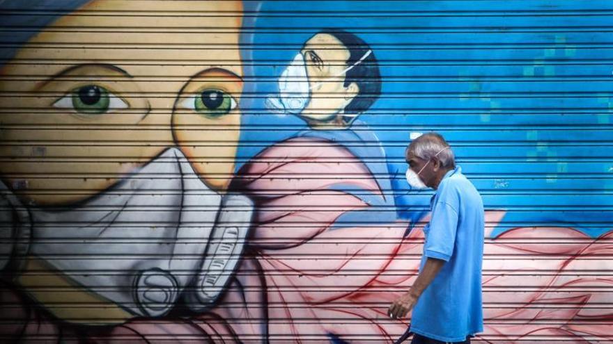 Un hombre con mascarilla pasa frente a un mural en Buenos Aires (Argentina).