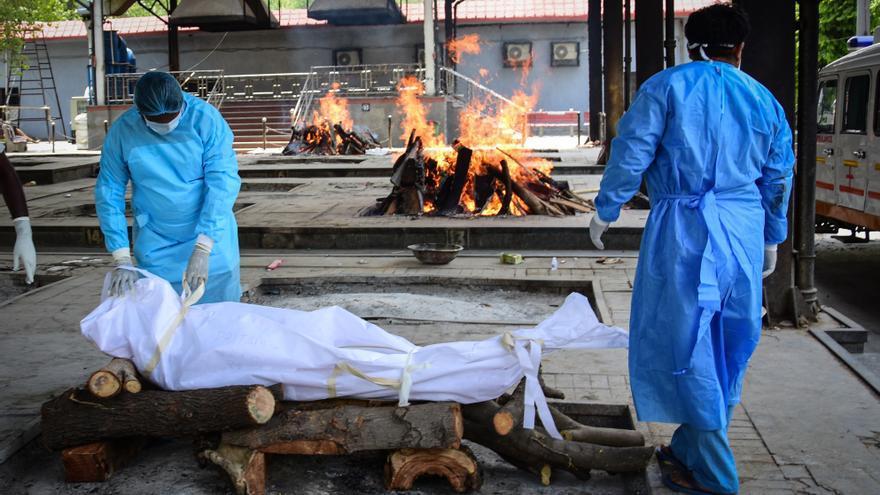 Trabajadores sanitarios queman cadáveres de personas fallecidas por coronavirus en Nueva Delhi, India