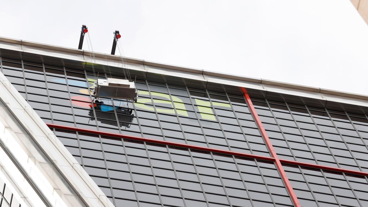 Operarios sustituyen uno de los rótulos de Bankia por otro de la nueva CaixaBank en las torres Kio de Madrid, sede operativa del banco nacionalizado estos últimos años. EFE/Zipi/Archivo