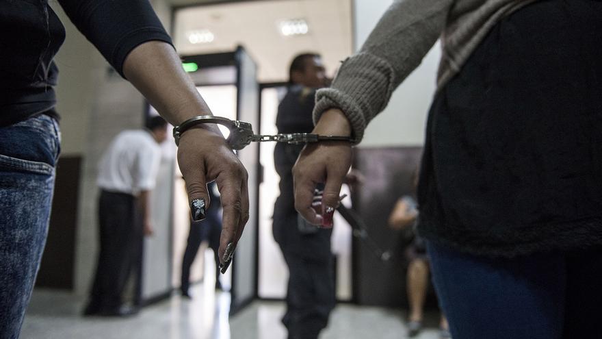 Hera, señalada de ser administradora de una célula de la pandilla MS13, y otra acusada por el mismo caso, llegan esposadas a la sala donde tendrá lugar la audiencia en el décimo tercero nivel de la Torre de Tribunales.