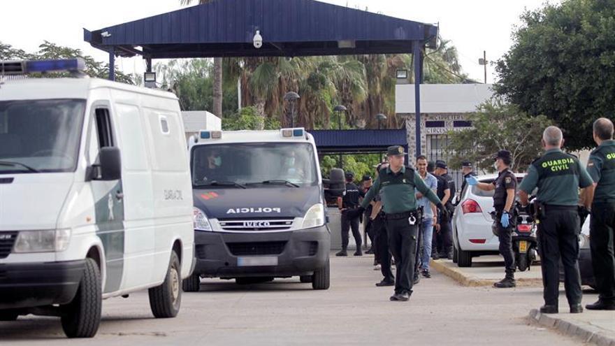 Efectivos de la Guardia Civil y Policía Nacional trasladan a los migrantes de origen subsahariano tras el salta a la valla de este domingo.