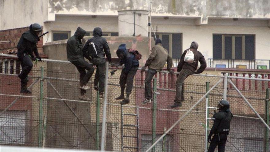 Imagen de archivo: varias personas encaramadas a la valla de Melilla   Efe