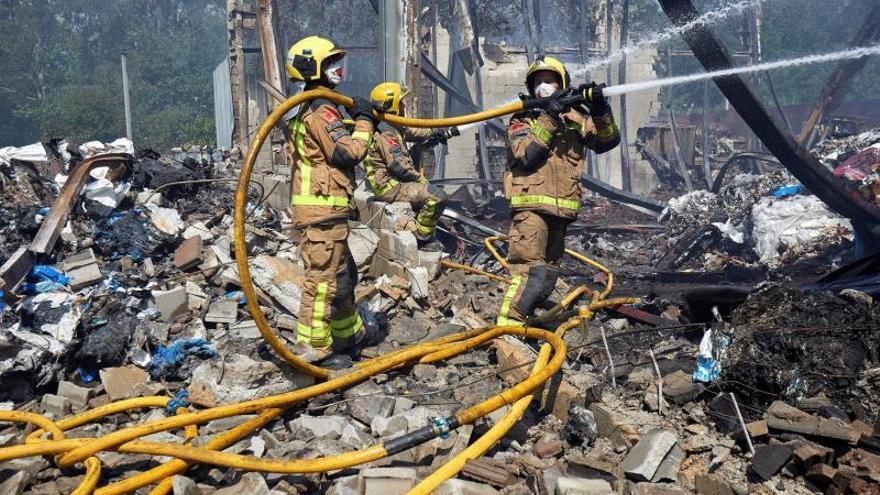 Los bomberos trabajan contra el fuego en una nave industrial de Girona