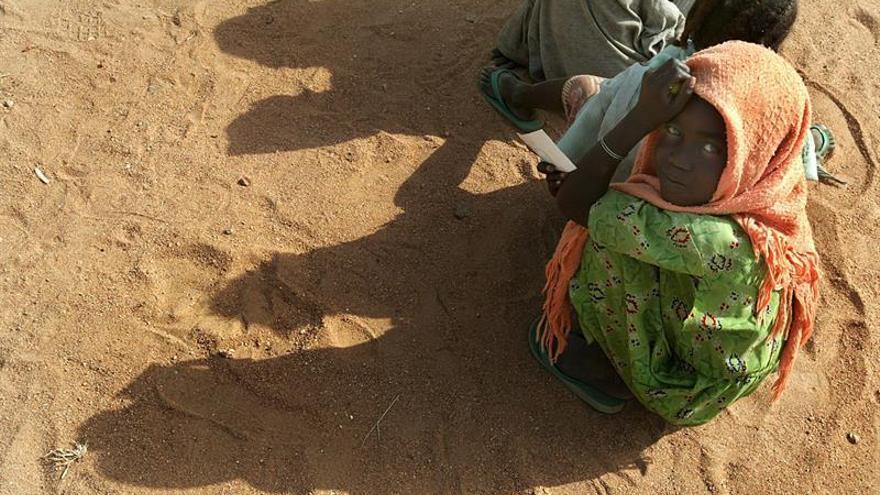 Niños refugiados sudaneses esperan comida y ropa en el campo de refugiados de Muhjar.