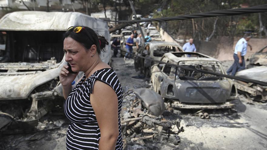Una mujer habla por teléfono en medio de varios coches quemados en Mati, al este de la capital griega