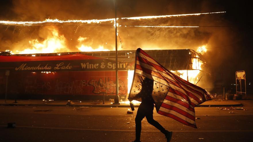 Un manifestante porta una bandera de Estados Unidos al revés, una señal de dolor, junto a un edificio en llamas el jueves 28 de mayo de 2020 en Minneapolis.