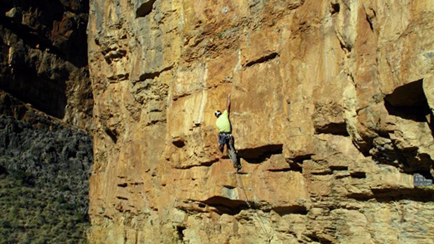 Asegurador atento a la escalada con la cuerda activa justa para evitar que el escalador toque el suelo en caso de caída. Ambos llevan el casco en una escuela andaluza donde caen piedras sueltas durante la escalada.