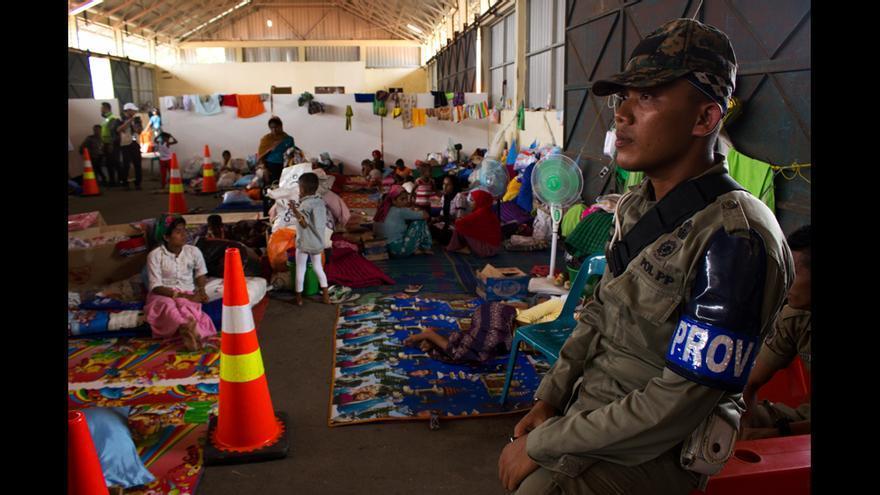 Un policía indonesio vigila el campo de refugiados de Kuala Langsa Port, en Aceh (Indonesia), donde se hospedan 677 personas, entre refugiados rohingyas y emigrantes bangladesíes. Los rohingyas y los bangladeshíes viven en pabellones separados, ya que se produjeron peleas entre ambos grupos cuando navegaban en el mismo barco en el Mar de Andamán. Los bangladesíes probablemente serán repatriados, pero el futuro de los rohingya es mucho más incierto, ya que el Gobierno indonesio sólo se muestra dispuesto a darles refugio un año, hasta que puedan ser trasladados a otros países. © Carlos Sardiña Galache / Yayasan Geutanyoe – A Foundation for Aceh.