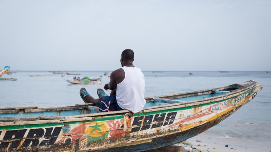 Un hombre descansa en una piragua en  Thiaroye-sur-mer, comuna de Dakar desde la que salieron a principios de los 2000 cayucos hacia Canarias.