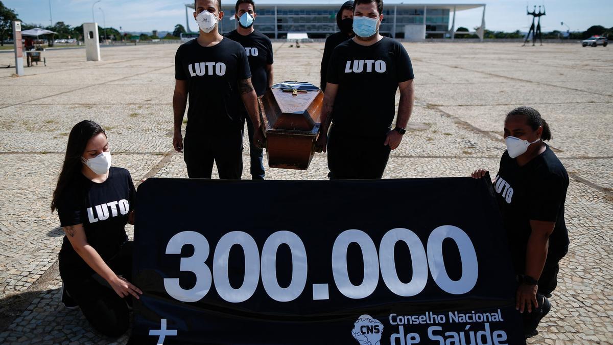 Protesta por los 300.000 muertos por Covid-19 en Brasil, donde se reinstauró la ayuda a los más pobres.