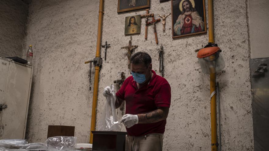 Un empleado del crematorio de San Isidro prepara las cenizas de una persona que murió con una infección de coronavirus para entregarlas a sus familiares.