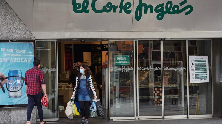 Una mujer saliendo con varias bolsas de El Corte Inglés