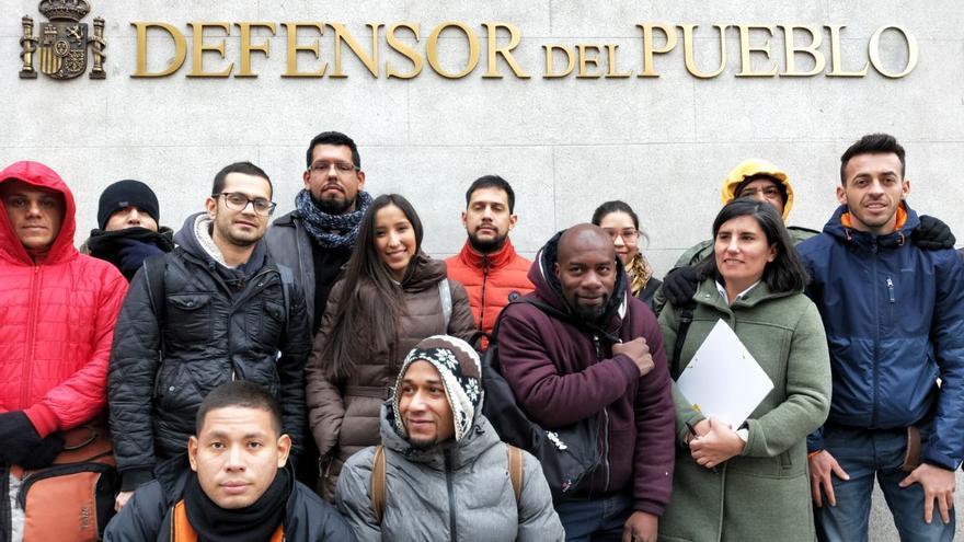 Personas solicitantes de asilo y la abogada de la Coordinadora de Barrios, Patricia Fernández, ante la sede del Defensor del Pueblo, en Madrid.
