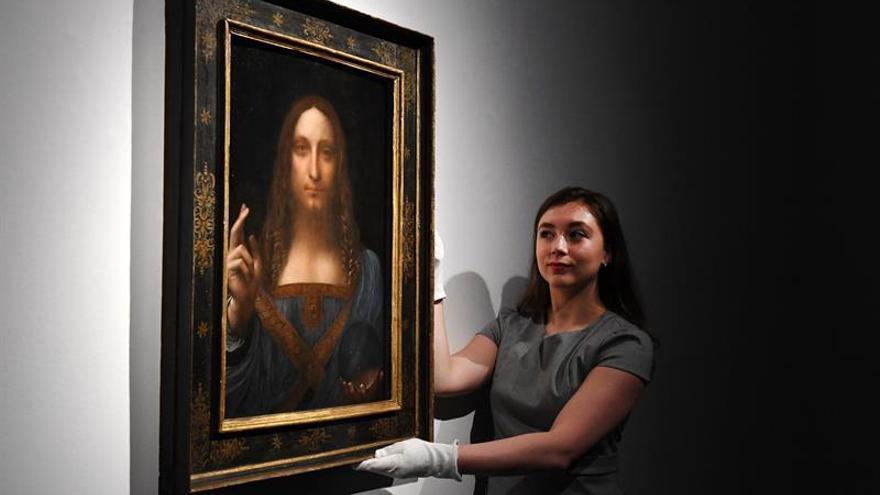 Una operaria de la casa de subastas Christie's coloca la obra de Da Vinci 'Salvator Mundi'