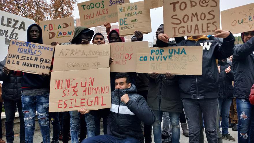 """Varios jóvenes extranjeros alzan carteles """"por una convivencia en paz"""", este domingo."""