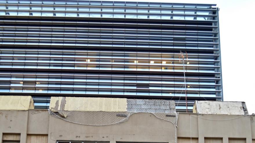 Al lado de la reluciente Ciudad de la Justicia las cornisas de las viviendas corren riesgo de desprendimientos. FOTO: Iago Otero Paz.