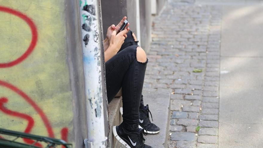 Una adolescente mira su teléfono móvil.