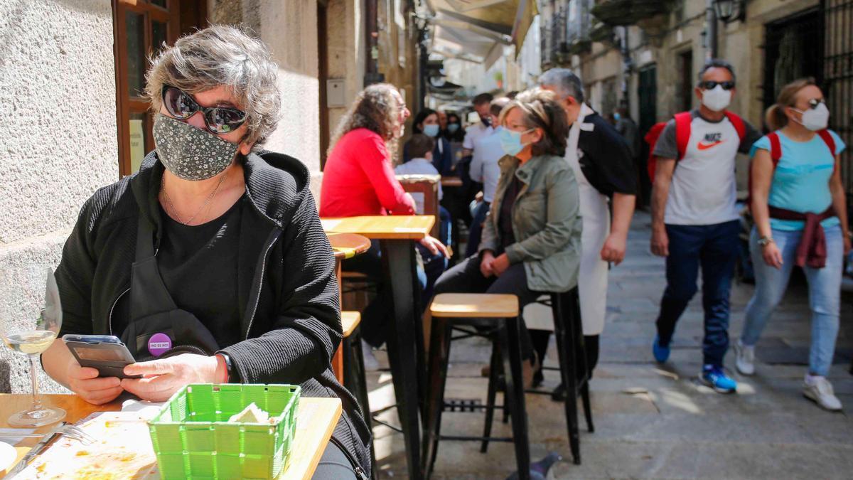 Archivo - Varias personas en una calle de terrazas de Baiona, en Vigo, Pontevedra, Galicia (España), a 28 de marzo de 2021.