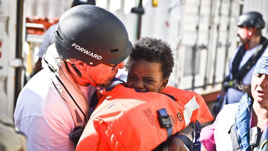 Pete Brindle, coordinadrs del Bourbon Argos, sostiene a un niño pequeño durante el rescate // Copyright: Sara Creta/MSF