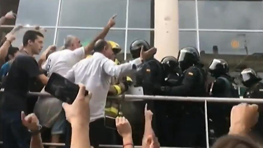 Votantes del 1-O bloquean el acceso de la policía en un colegio electoral en un vídeo ofrecido por la fiscalía en el juicio.