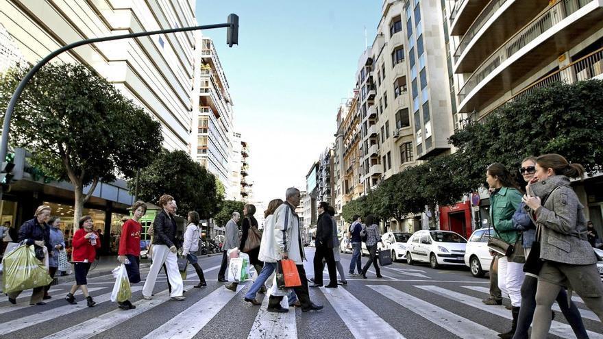 Diferentes personas cruzan por un paso de peatones en la calle Colón de Valencia